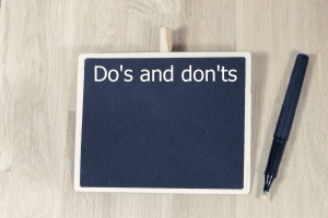 sentence do's and don'ts written with chalk on a blackboard, on a table with pen